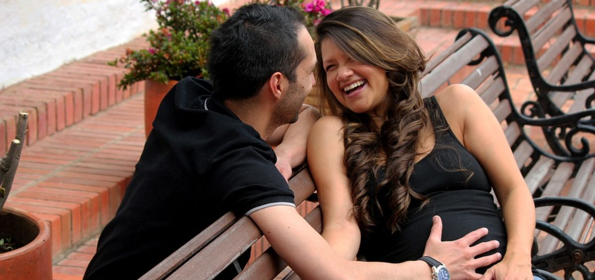 Pregnany Couple Laughing On Bench