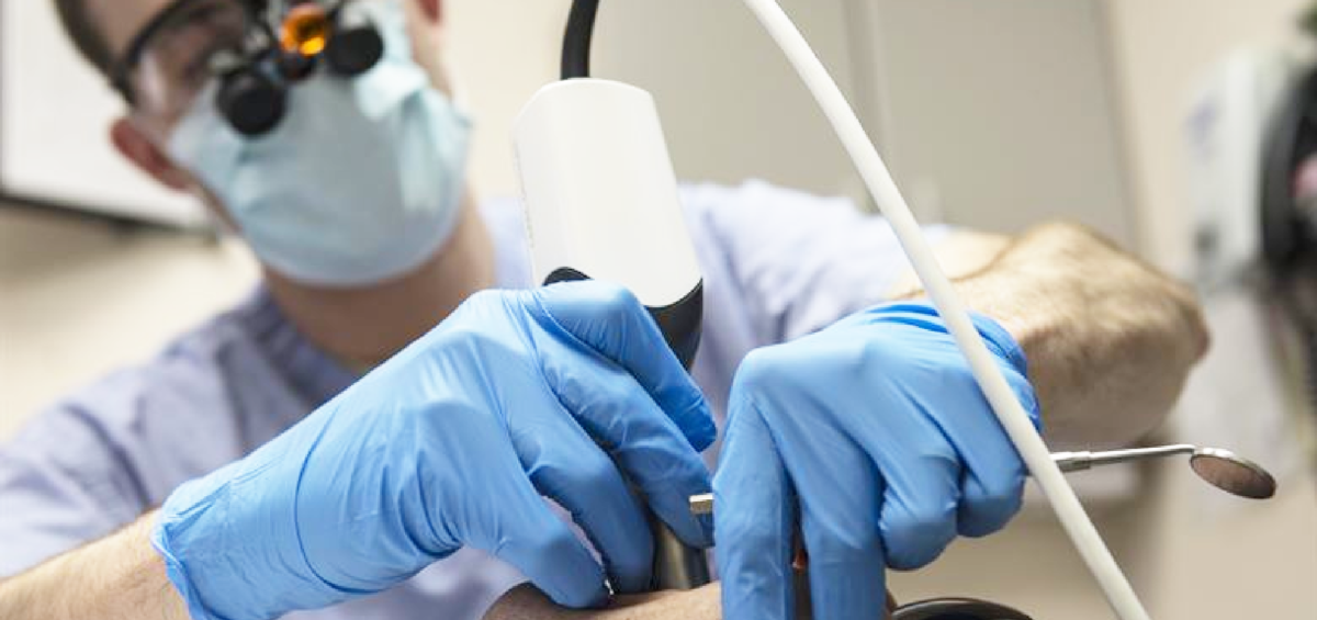Dentist using optical scanner on patient